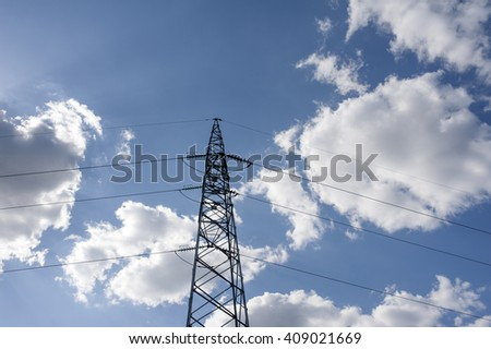 Electricity transmission pylon silhouetted against blue sky #409021669