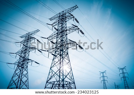 electricity transmission pylon silhouetted against blue sky at dusk  #234023125