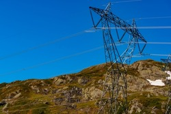 Electricity transmission pylons, power lines high voltage towers in norwegian mountains landscape.