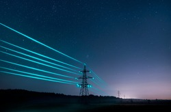 Electricity transmission towers with glowing wires against the starry sky. Energy concept.