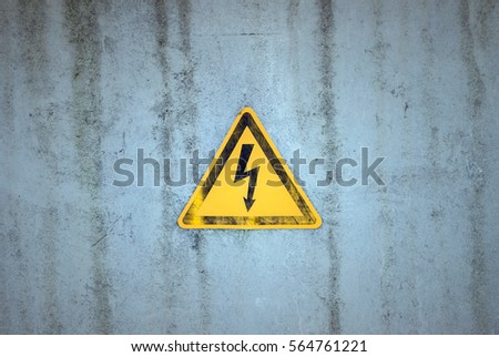 Electricity warning sign on a weathered background #564761221