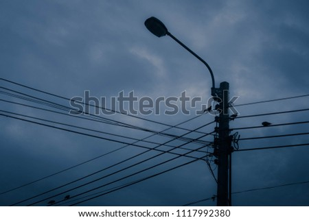 Electricity wire and pole with dark blue clouds and sky background #1117992380