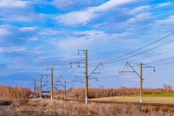 Electrified railway on the background of a blue sky with clouds. Soft Focus
