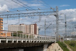 Electrified railway on the background of a residential building, wires carrying steel trusses are visible, a bridge over the highway