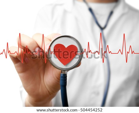 Electrocardiogram, red heart and female hand with stathoscope, closeup. Cardiology concept.