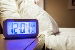 electronic alarm clock stands on a bedside table in the room or hotel room