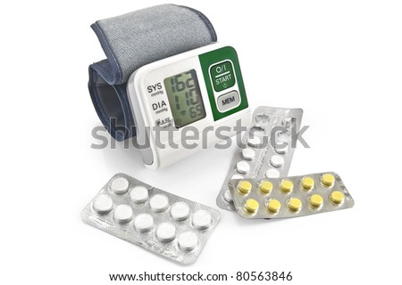 Electronic blood pressure monitor for a hand with pills in the package is isolated on a white background