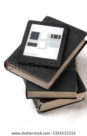 electronic book on top of pile books. Modern e-book and ordinary books. Copy space. Training and technology concept. Concept of reading, learning new knowledge, self improvement. Evolution of reading.