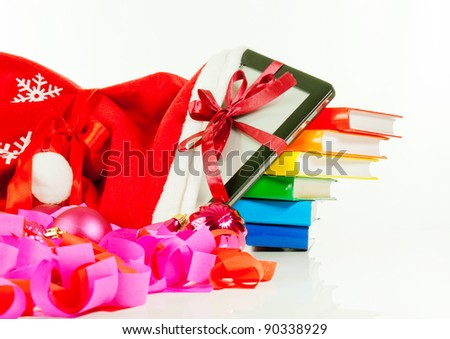 Electronic book reader with stack of books in bag against white background