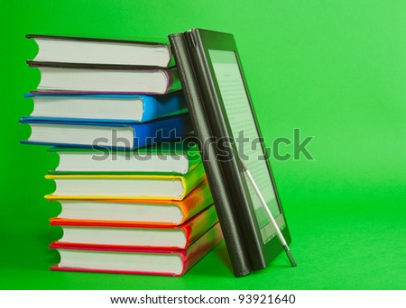 Electronic book reader with stack of printed books over green background