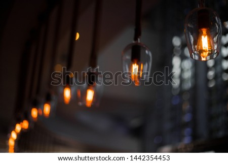 Electronic Bulb Light hanging in Restaurant softdrink Bar decor, decoration of garland with light bulb classic design and blurred line of sight along to edge room, incandescent decorate in the shop