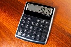 Electronic calculator isolated on a dark wood backgroud displaying 2019