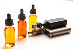 Electronic cigarettes and bottles of yellow liquids. Vaping accessories on a white table. The concept of vaping. Smoking electronic cigarettes. Sale of Smoking accessories. Gadgets for Smoking.