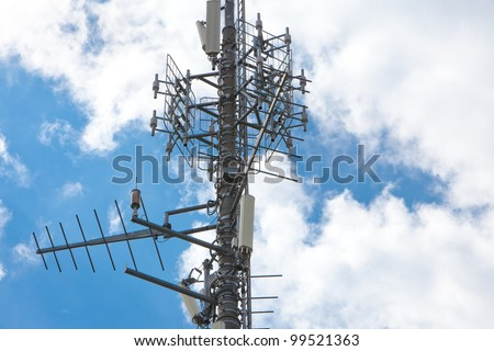 Electronic communications and cell phone tower under partially cloudy sky. Horizontal format