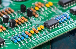 Electronic components. Integrated circuits, resistors, transistors and capacitors on PCB. Green copper board detail. Standard color code. Old computer hardware. Electrotechnology. Waste sorting. Eco.