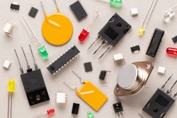 Electronic components on a beige background. There are microcontrollers, transistors, yellow and red LEDs, microcircuits, thyristors, capacitor.