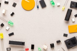 Electronic components on a beige background with copy space centered. There are microcontrollers, transistors, yellow and red LEDs, microcircuits, thyristors, capacitor.