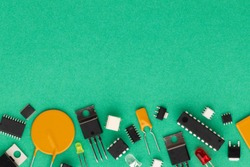 Electronic components over green background with copy space. There are microcontrollers, transistors, yellow and red LEDs, microcircuits, thyristors, capacitor.