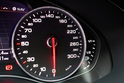 Electronic dashboard of modern luxury car view from aside. Speedometer shows speed in kilometers per hour and fuel control, parking and GPS system alert with copyspace.