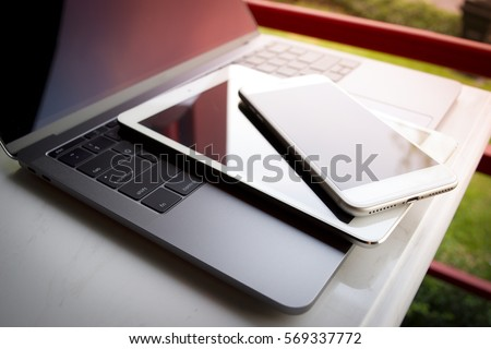 Electronic device mobile phone tablet computer laptop keyboard on table. White smartphone at office store desk technology business background. - Shutterstock ID 569337772