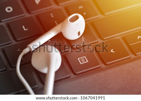 Electronic devices. Headphones on the keyboard. Online straming music service concept #1067041991