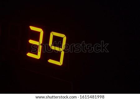 Electronic digital scoreboards. Digital LCD Stopwatch Timer. Orange luminous numbers on a black background