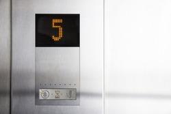 Electronic display inside elevator informs five floor