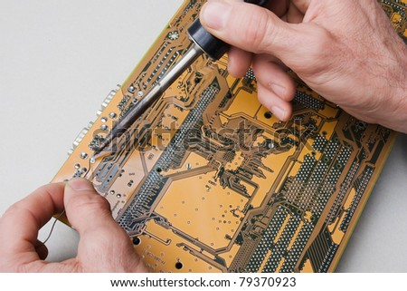 electronic laboratory - technician repairs circuit board of computer with iron soldering and tin wire