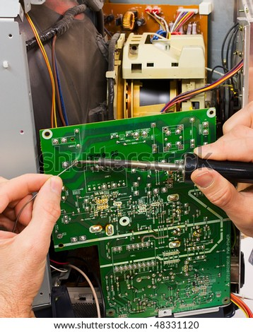 electronic laboratory, technician repairs circuit board of tube television with iron soldering and tin wire