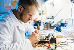 Electronic laboratory worker connects cirquit board with wires and clamps for testing and metering. Man in white robe and protective glasses working at desk. Blue and white color scheme.