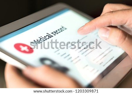 Electronic medical record with patient data and health care information in tablet. Doctor using digital smart device to read report online. Modern technology in hospital.