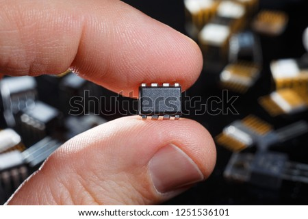 Electronic microchip with fingers close-up. Man hand holds microcircuit.