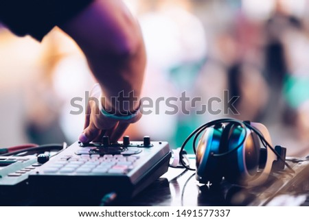 Electronic music festival in summer.EDM dj plays set on stage at concert.Disc jockey playing popular music on midi controller device & headphones on table.Professional audio equipment for djs