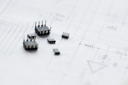 Electronic parts on the background of the schematic diagram. Microchips, transistors, integrated circuits.Design of electronic circuit and electronic Board.Connection diagram.Small depth of field