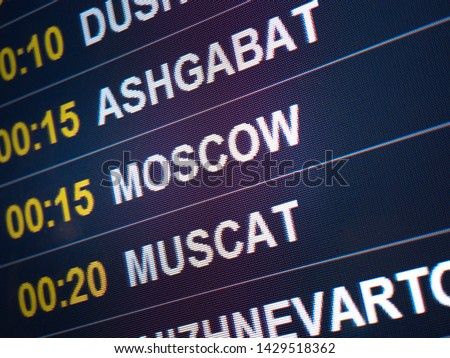 Electronic scoreboard flights and airlines. Destinations: Ashgabat, Moscow, Muscat. Airport flight information arrival displayed on departure board, flight status changing