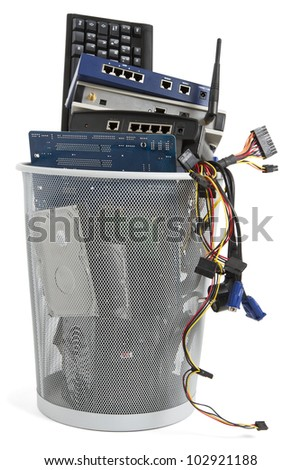 electronic scrap in trash can. keyboard, power supply, router, cables, logicboard, hard drive, switch