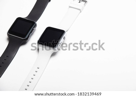 Electronic wrist watch on a white background . White and black wrist watches. Women's and men's watches. Isolated background. Article about modern watches. Article about choosing a watch.