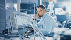 Electronics Development Engineer Working on Computer, Designing Motherboard, Doing Maintenance of Devices and Soldering Circuit Boards. Professionals working in Bright and Modern Office