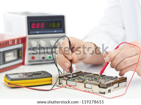 Electronics engineer testing computer part in electronics workshop