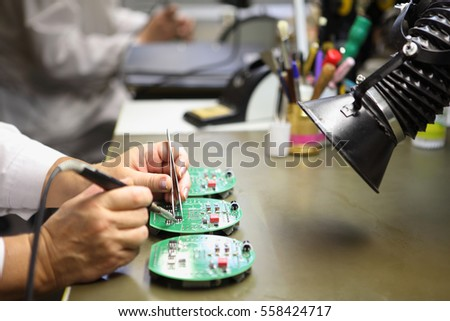 Electronics Manufacturing Services, Manual Assembly Of Circuit Board Soldering,  close-up of the hand women hold tool.