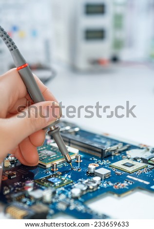 Electronics repair service, hand of female tech fixes an electronic circuit, text space