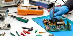 Electronics repair service-the master checks the electronic unit and performs electrical measurements.Oscilloscope and multimeter measuring instruments.