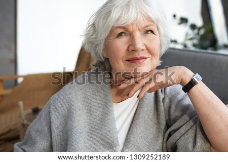 Photo of Elegance, age, beauty and people concept. Indoor image of charming elegant senior mature woman enjoying free time at home, sitting on couch in stylish living room interior, smiling happily