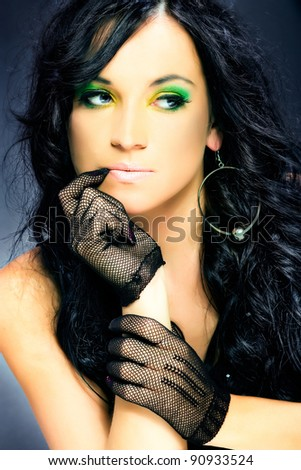 elegance beauty dark hair woman with lace gloves on hands, fashion model showing her green and yellow makeup, studio shot on dark background