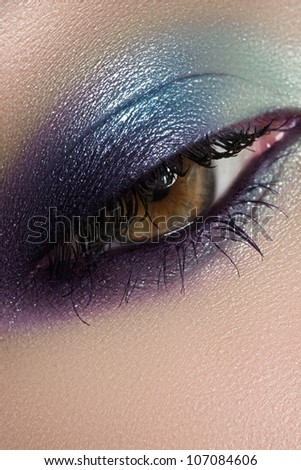 Elegance close-up of beautiful female eye with marine colors eyeshadow. Macro shot of face part