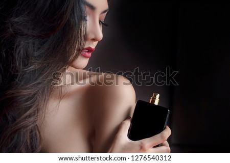 Elegance Sexy Sensual Beautiful Woman Applying Paris, France Luxury Black Bottle fragrance perfume . Young Elegant Girl  Red Lips on dark background. #1276540312