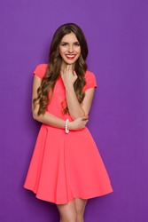 Elegance young woman in pink mini dress posing with hand on chin and looking at camera. Three quarter length studio shot on purple background.