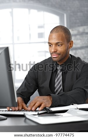 Elegant afro businessman concentrating on working on computer at office desk.
