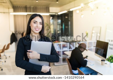 Elegant and cheerful businesswoman. Cheerful young beautiful woman in glasses looking at camera with smile while sitting at her working place #1410290564