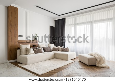 Elegant and comfortable designed living room with big corner sofa, wooden floor and big windows Stockfoto ©